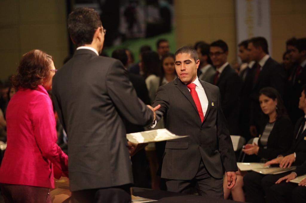 hombre de traje negro y corbata roja recibe diploma de dos personas