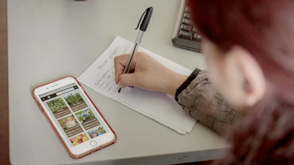 Mujer escribiendo sobre un escritorio al lado de un smartphone