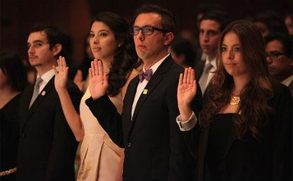 varias personas levantan la mano como señal de un juramento que están haciendo