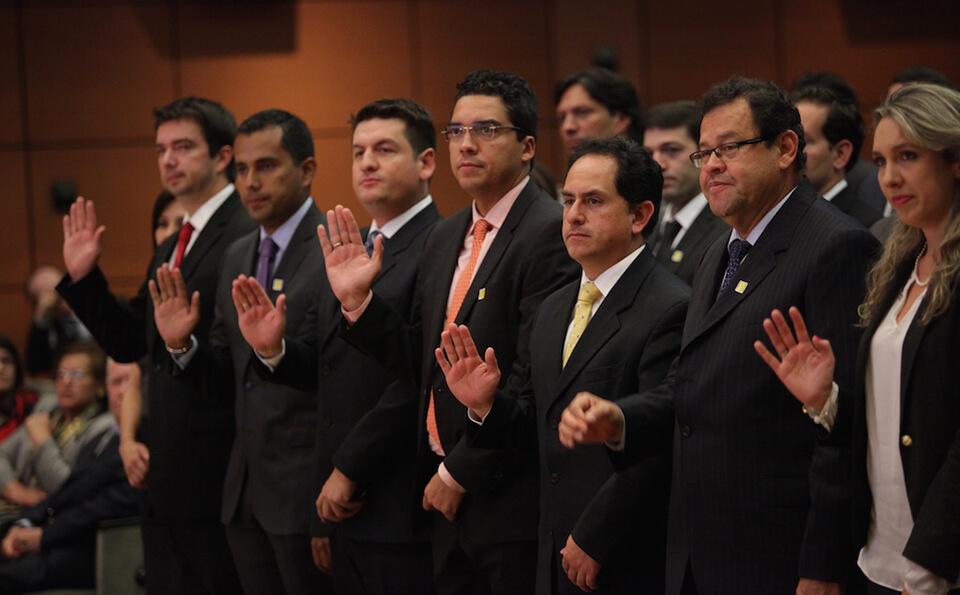 hombres levantaron la mano para hacer juramento en un auditorio