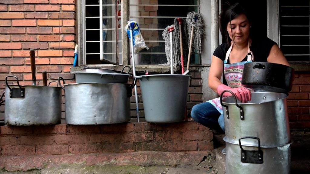 Mujer lavando ollas.