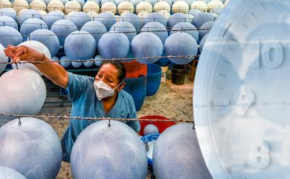 Una mujer arregla unos balones de fútbol, en una fábrica. A un lado un reloj.