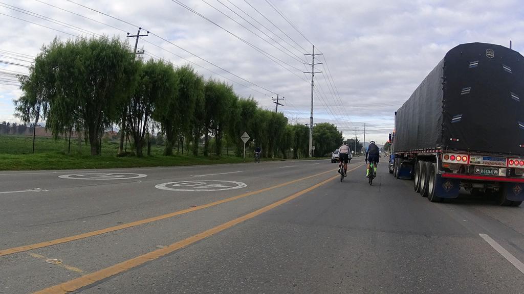 Dos ciclistas al lado de un camión.