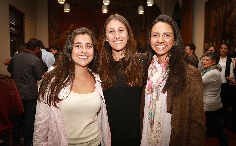 tres muejres se abrazan y sonríen en forma de celebración durante un evento