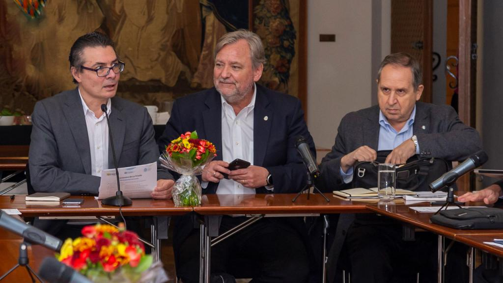 Tres hombres sentados.