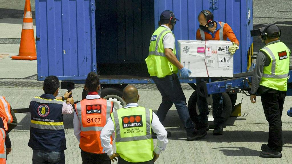 Personas cargando caja con vacunas en un container