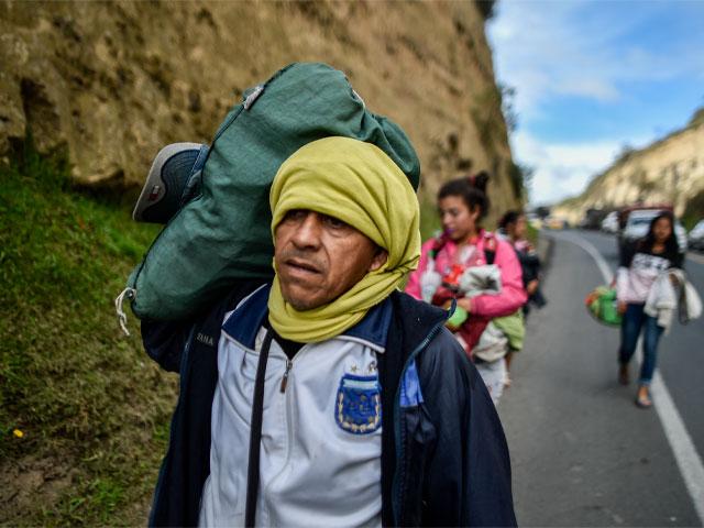 Hombre con la cabeza tapada camina por una carretera.