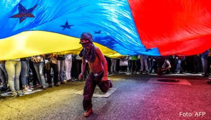 Protestas en Venezuela, un joven corre bajo una bandera venezolana.