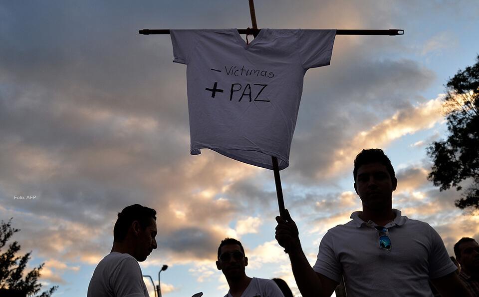 joven con camiseta blanca levanta cruz, en la cruz está puesta una camiseta con la que piden paz