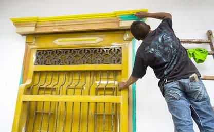 Hombre pinta una ventana de una casa de color amarillo.