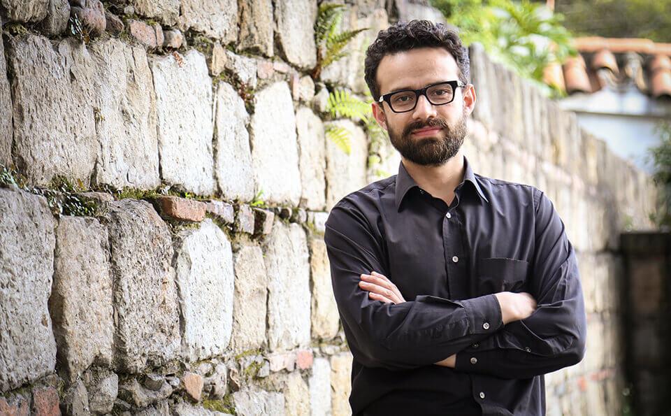 hombre de gafas cruzado de brazos usando camisa oscura. Atrás vemos un muro de piedra